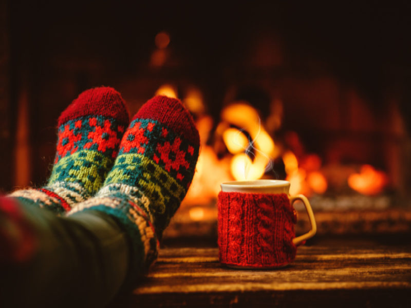 Feet in front of a fire with mug