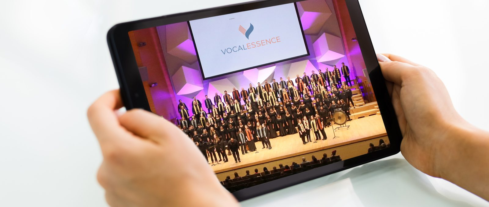 Hands holding tablet with image of many singers performing on stage