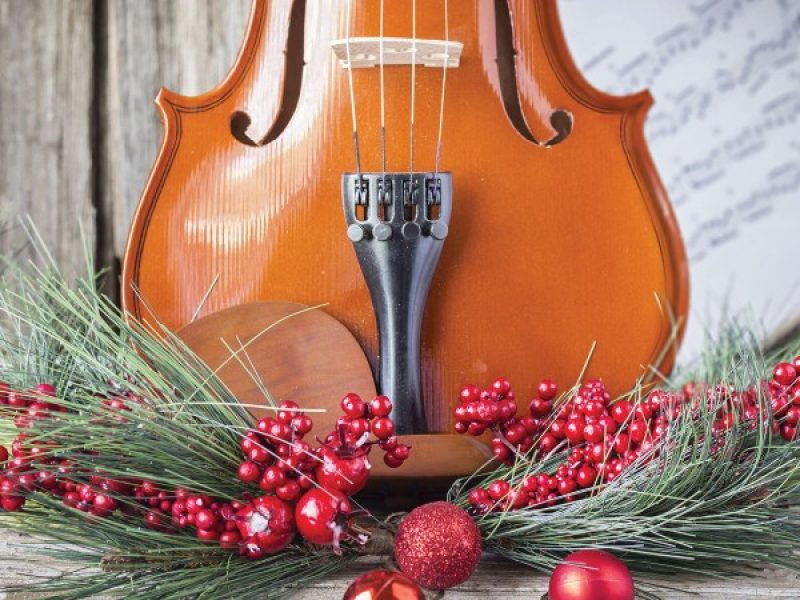 Violin in front of sheet music with pine, red berries, and red ornaments