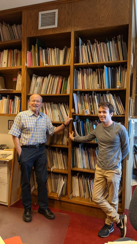 Philip Brunelle and Aaron Schondorf pose in front of shelves of music.